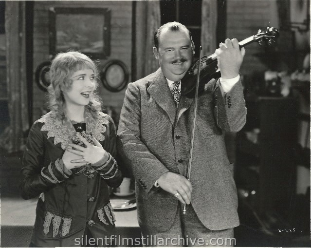 "Colleen Moore, starring in ""Twinkletoes,"" First National film, reacts to the violin solo rendered by Paul Whiteman, the eminent orchestra leader, composer and idol of American music fans. (1926)"